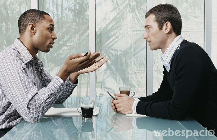 Two Businessmen Sitting and Talking Face to Face in a Meeting
