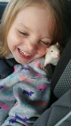 una niña y una rata blanca